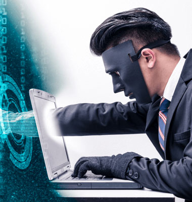 Man with a mask putting his gloved hand through a laptop