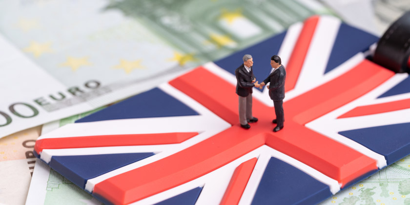 Two business men figures shaking hands on a GB flag suitcase label