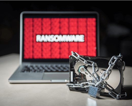 A Physically locked up hard drive next to a laptop with ransomware