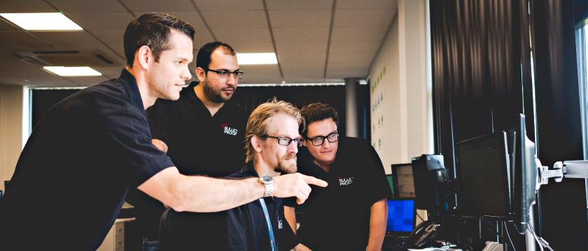 Bulletproof engineers looking at a computer